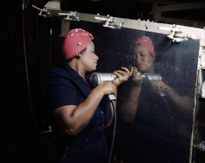 "A for real ""Rosie the Riveter"" operating a hand drill working on an A-31 Vengeance dive bomber."