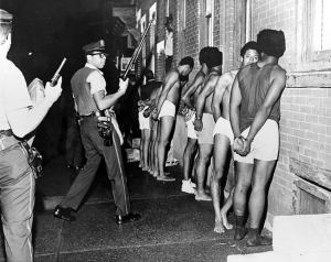 Members of the Black Panther Party, stripped, handcuffed, and arrested after Philadelphia police raided the Panther headquarters, August, 1970.  Credit - Urban Archives, Temple University